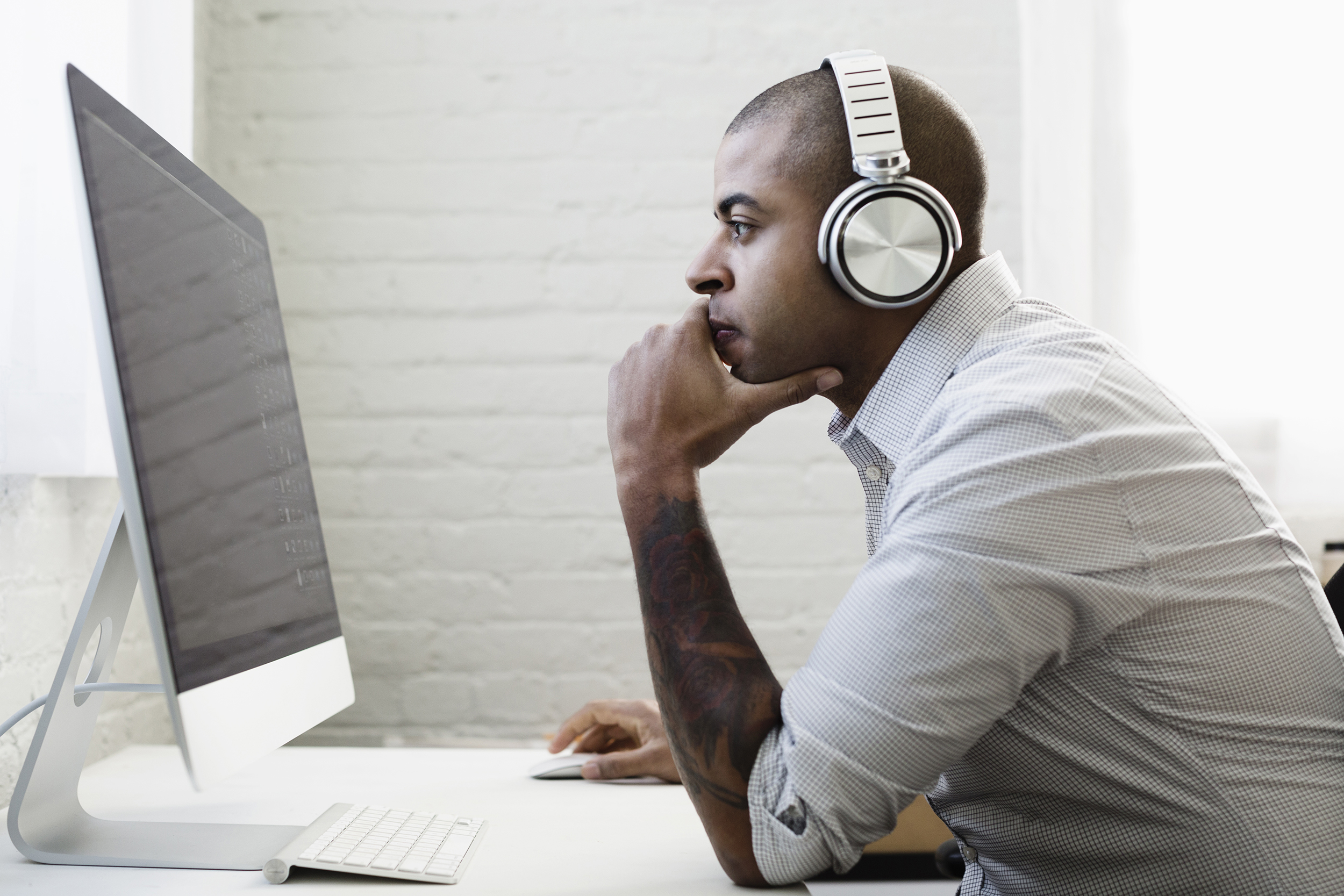 Mixed Race Businessman Listening To Headphones And Working At Desk